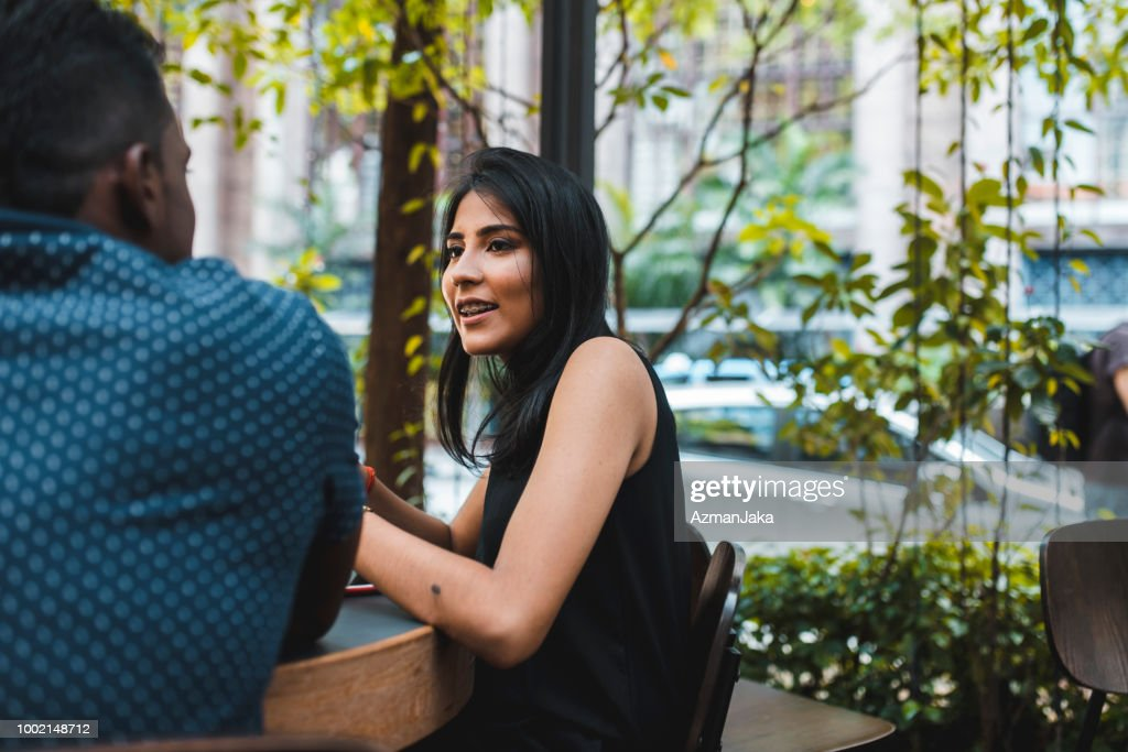 Two People Talking Outdoors At A Cafe High Res Stock Photo Getty Images