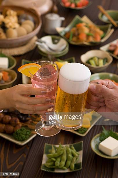 Two People Toasting with Beer and Cocktail at Izakaya