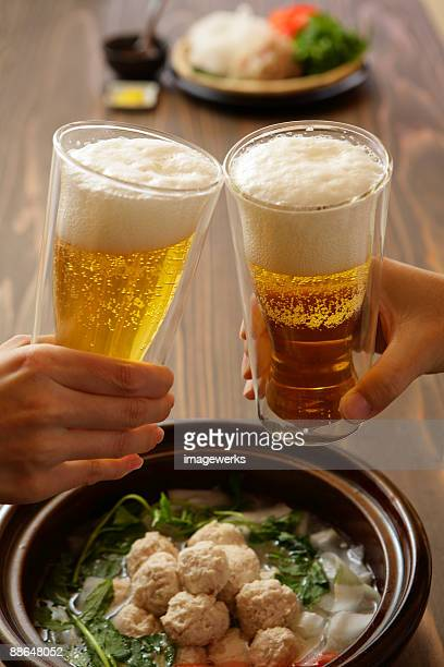 Two people toasting with beer, close-up