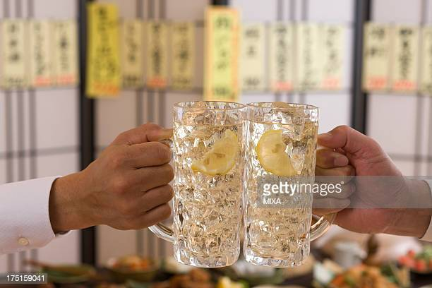 two people toasting with whisky and soda at izakaya - beer stein stock photos and pictures