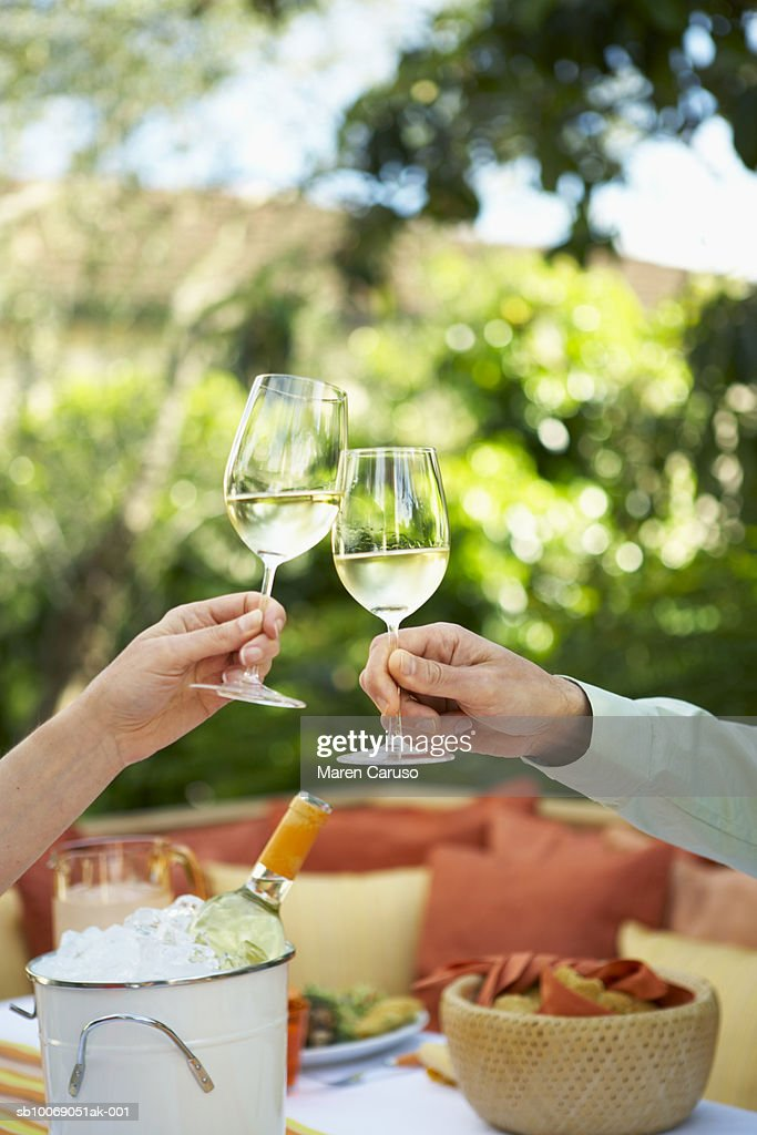Two people toasting with white wine : Stockfoto