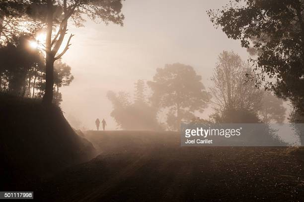 Two people trekking at sunrise in misty forest in Burma