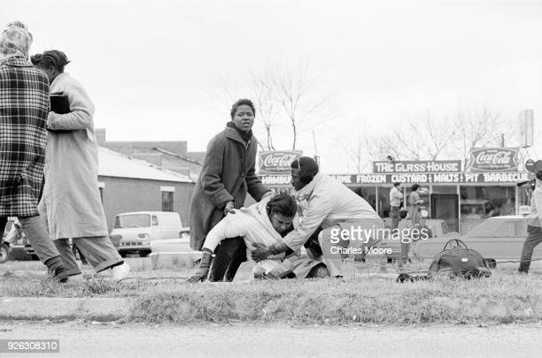 Two people try to lift the unconscious body of Civil Rights activist Amelia Boynton at the base of the Edmund Pettus Bridge during the first Selma to...