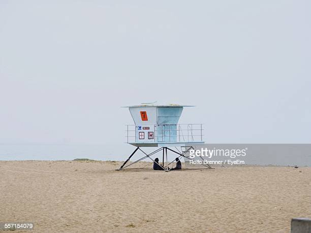 Two People Under Lifeguard Hut On Beach