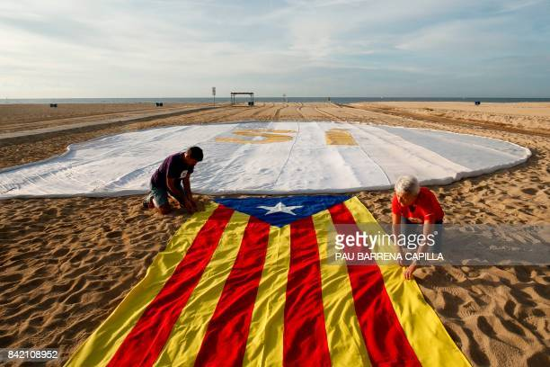 Two people unfold an Estelada beside a banner reading SI on El Masnou beach near Barcelona on September 3 during an action called by ANC to support a...
