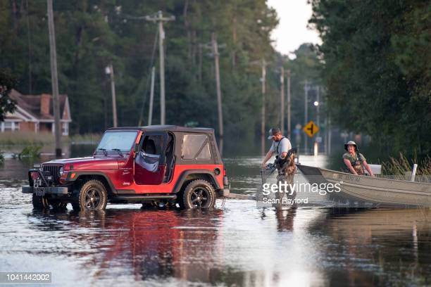 Two people use a neighborhood street as a boat ramp in floodwaters from the Waccamaw River caused by Hurricane Florence on September 26, 2018 in...