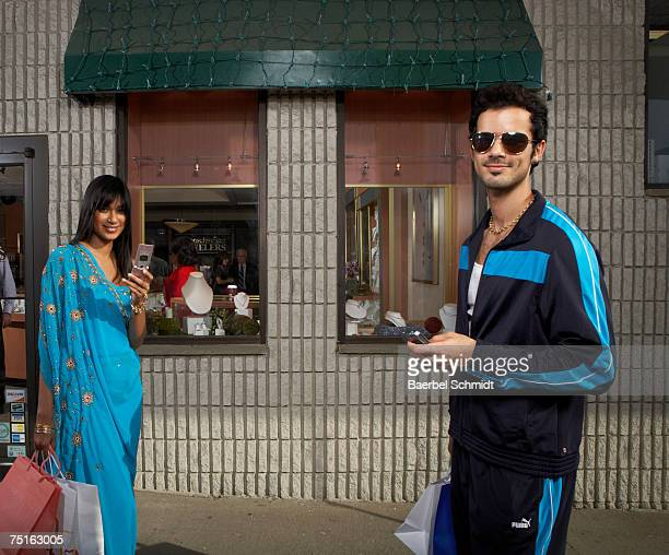 two people using mobile phones while walking past jewellery store - trainingsanzug stock-fotos und bilder