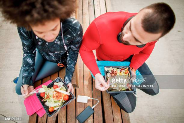 two people using plastic eating utensils to eat a healthy protein salad from a plastic casing, with a mobile phone attached to a power bank between them - plastic plate stock photos and pictures