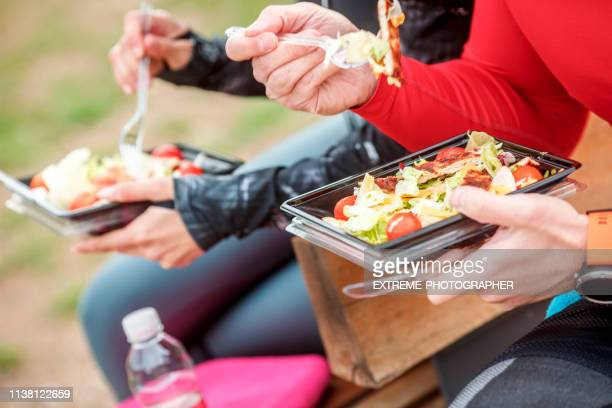 two people using plastic eating utensils to eat a healthy protein salad from a plastic casing - plastic plate stock photos and pictures