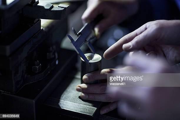 Two people using Vernier caliper in workshop to measure diameter