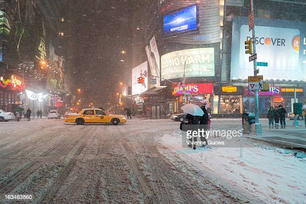 CONTENT] Two people wait under a shared umbrella under the lights of Times Square while snow falls and a yellow taxi cab passes through the...