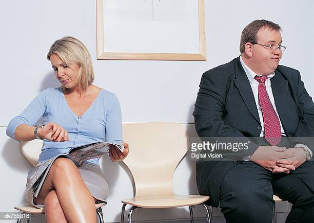 two people waiting in a doctor's office - fat woman sitting on man stock pictures, royalty-free photos & images