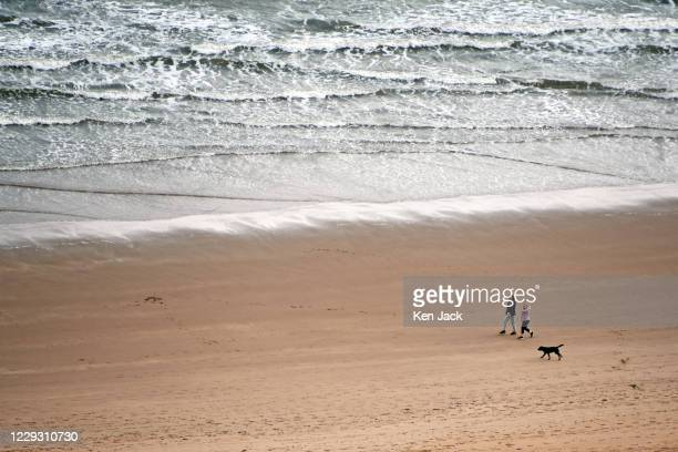 Two people walk a dog on the beach below the cliffs at St Cyrus National Nature Reserve on October 27, 2020 in St Cyrus, Scotland.