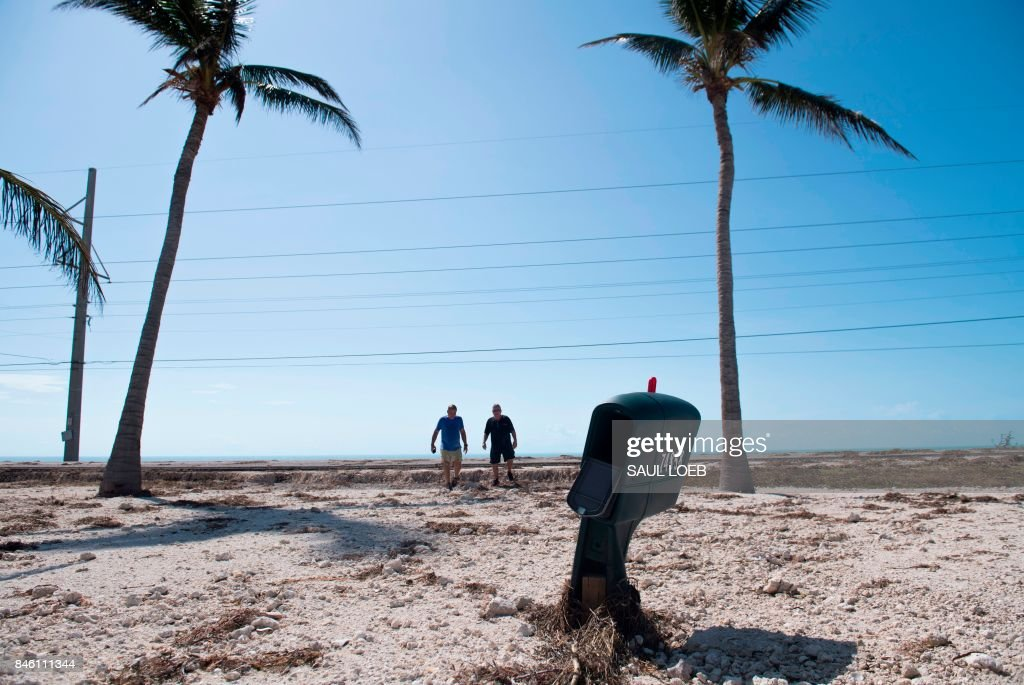 TOPSHOT - Two people walk across a street covered in sand by Hurricane Irma in Islamorada, in the Florida Keys, September 12, 2017. /