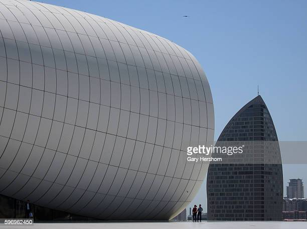 Two people walk across the plaza at the Zaha Hadid designed Heydar Aliyev Center next to the Trump Tower in Baku Azerbaijan May 3 2014