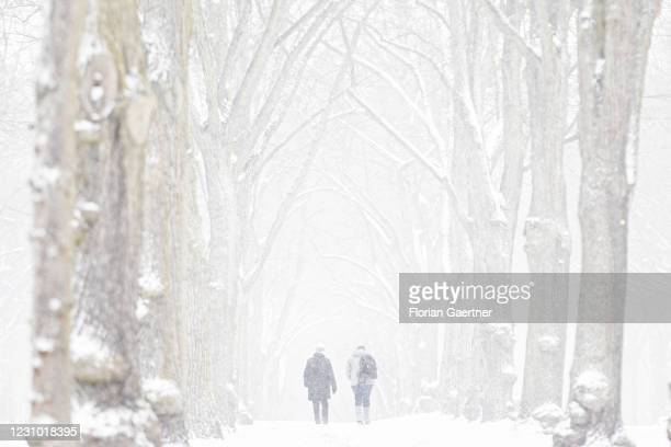 Two people walk along an avenue during heavy snow storm on February 07, 2021 in Berlin, Germany.