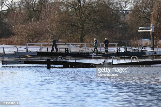 """Two people walk along the flooded lock on December 27, 2020 in Worcester, England. """"Storm Bella"""" brought gales and heavy rain to the West Midlands,..."""