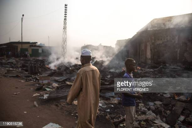 Two people walk among the burning rubbles in the Koudoukou market, in the PK5 district in Bangui on December 26 after clashes erupted when traders...