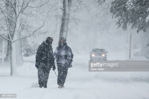 Two people walk down a street while a massive winter storm bears down on the region on January 4 2018 in Scituate Massachusetts The 'bomb cyclone'...