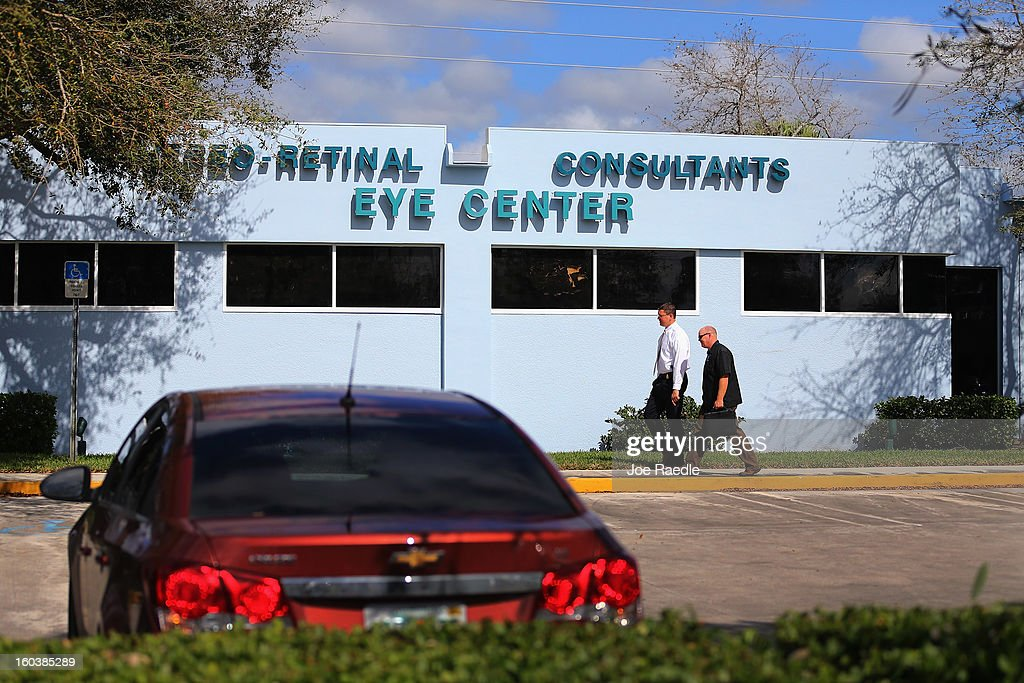 Two people walk in front of the medical-office complex of Dr. Salomon Melgen, who has possible ties to U.S. Sen. Bob Menendez (D-NJ), as FBI agents and other law enforcement officials investigate on January 30, 2013 in West Palm Beach, Florida. The agents arrived last night at the medical-office complex and started taking away potential evidence in several vans.