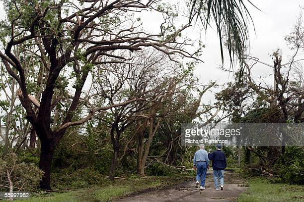 Two people walk in the retirement community of Century Village which suffered major wind damage to their landscaping during Hurricane Wilma on...