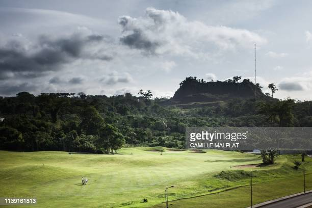 Two people walk on the green of the Sofitel Hotel to play golf in Sipopo nearly 16km from Malabo in Equatorial Guinea on April 20 2019 In Sipopo a...