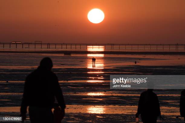 Two people walk out at low tide to watch the sunset over the pier as parts of the UK enjoyed warm weather on February 27, 2021 in Southend on Sea,...