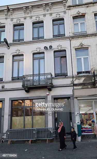 Two people walk past the Abdeslam family's apartment in Brussels' Molenbeek district close to the Town's Square where a vigil was earlier held on...