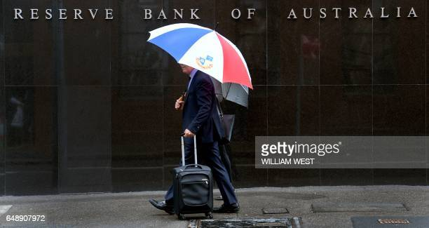 Two people walk past the Reserve Bank of Australia in Sydney on March 7 2017 Australia's central bank left interest rates at a record low of 150...