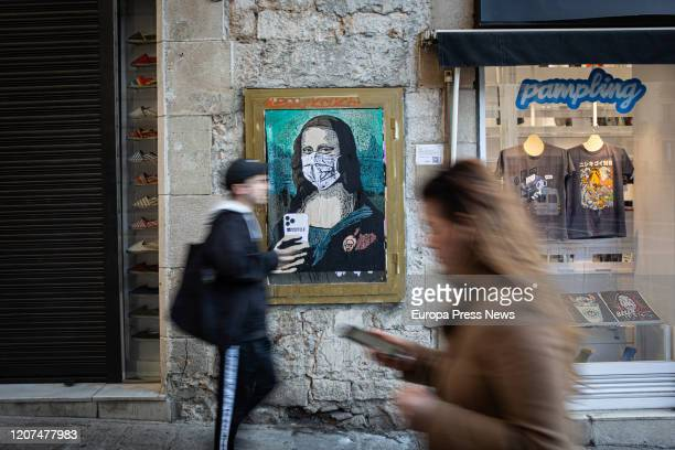 Two people walk with their mobiles next to the paint of a Mona Lisa with a mobile phone and a mask work of the graffiti artist TV Boy called 'Mobile...