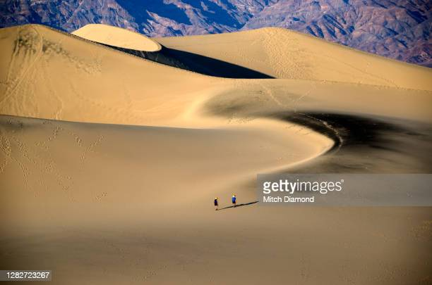 two people walking across sand dunes - great basin stock pictures, royalty-free photos & images