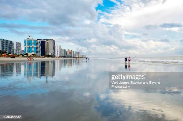 two people walking along shore reflections at myrtle beach, south carolina - file:myrtle_beach,_south_carolina.jpg stock pictures, royalty-free photos & images