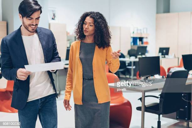 two people walking and talking in the office - side by side stock pictures, royalty-free photos & images
