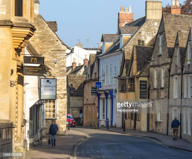 two people walking down a quaint shopping street in cirencester, gloucestershire, the cotswolds on a sunny autumn day - cirencester stock pictures, royalty-free photos & images