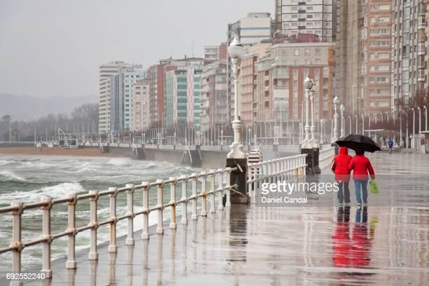 two people walking in gijon promenade during stormy day. gijón, asturias (spain) - gijon fotografías e imágenes de stock