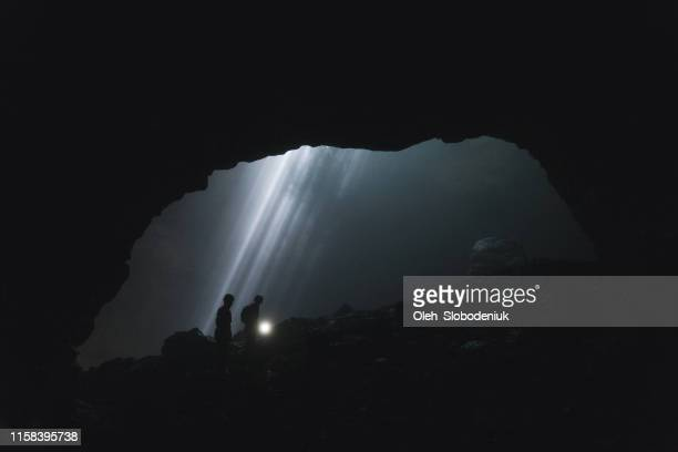 two people walking  in jomblan cave  on the background of sunbeams - cave stock pictures, royalty-free photos & images