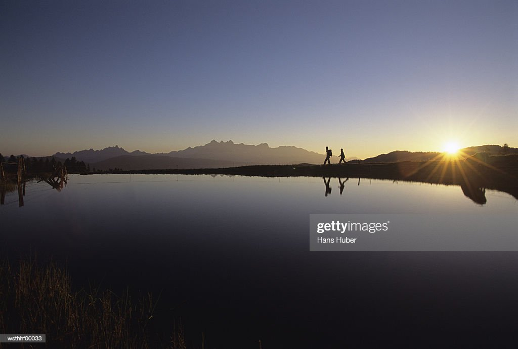 Two people walking near river bank, Austrian Alps, silhouette : Stock Photo