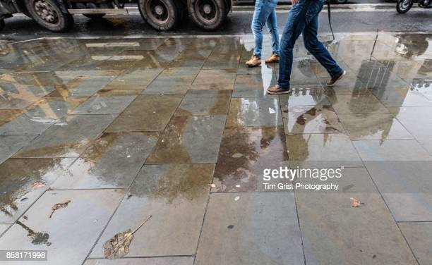 two people walking on a wet pavement - wet jeans stock photos and pictures