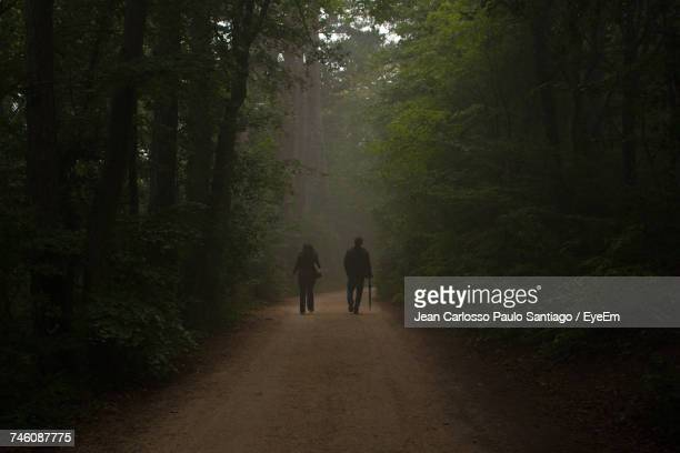 two people walking on country road along trees - middlebare afstand stockfoto's en -beelden