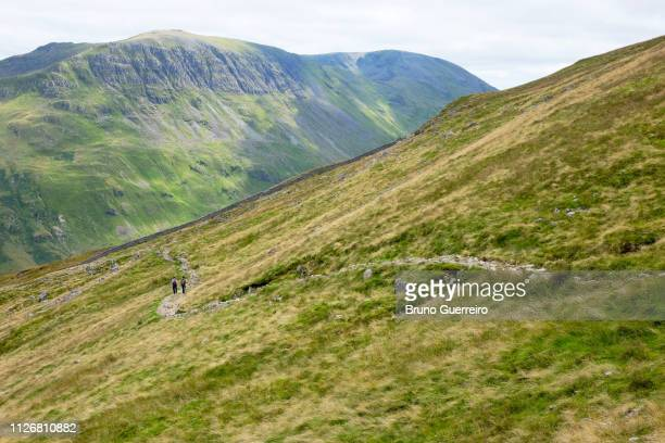 two people walking on hiking trail on lush green hillside at helvellyn in the lake district - lake district stockfoto's en -beelden