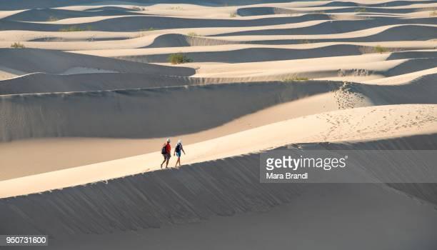 Two people walking on sand dunes, Mesquite Flat Sand Dunes, Death Valley, Death Valley National Park, California, USA