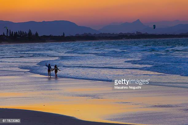 Two people walking on the sand beach of Byron Bay in the evening