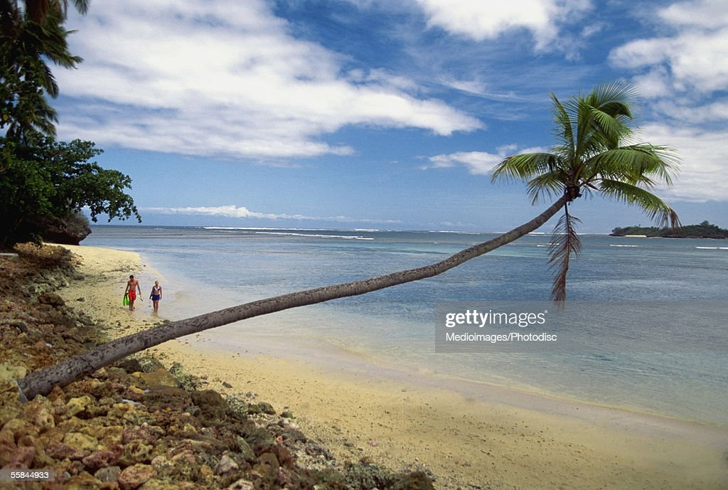 Two people walking on Warwick Resort Beach, Nadi, Viti Levu Island, Fiji : Stock Photo