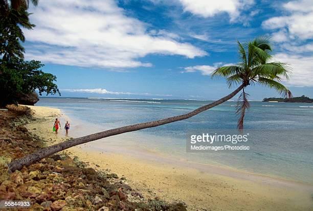 Two people walking on Warwick Resort Beach, Nadi, Viti Levu Island, Fiji