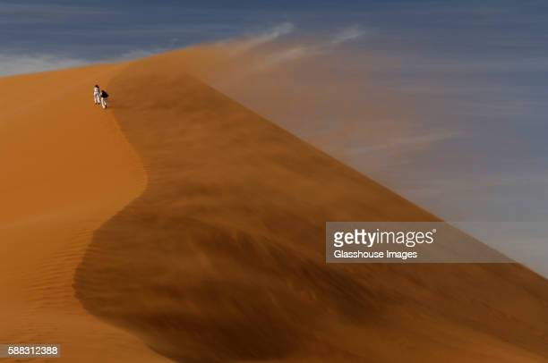 two people walking on wind swept sand dune - struggle stock pictures, royalty-free photos & images