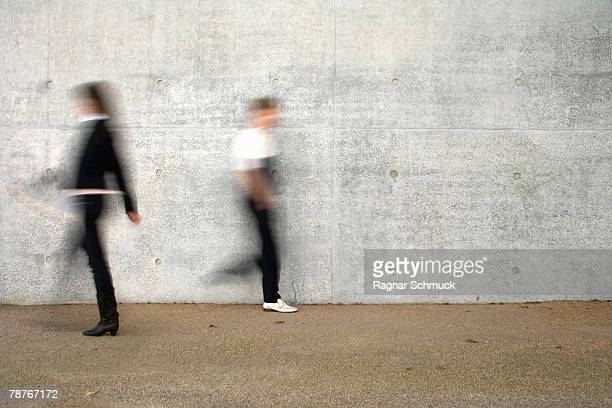 two people walking past a wall - moving past stock photos and pictures