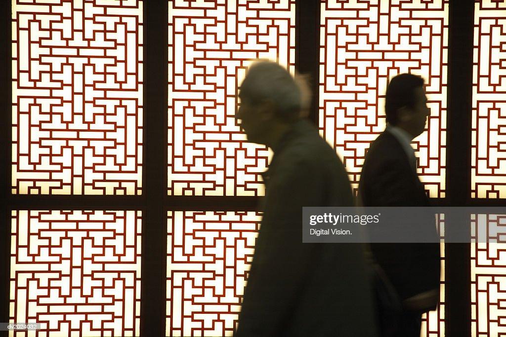 Two People Walking Past Ornate Panels, Japan : Stock Photo