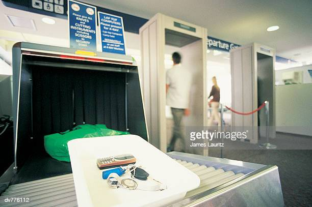 Two People Walking Through a Metal Detector at Airport Security