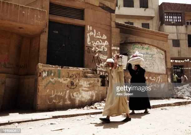 two people walking through a run down area of cairo. - alex saberi photos et images de collection