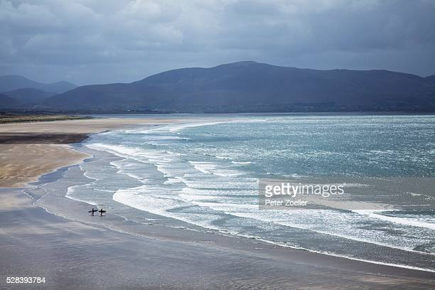 two people walking with surfboards on the beach in inch on the dingle peninsula; county kerry, ireland - inch stock pictures, royalty-free photos & images